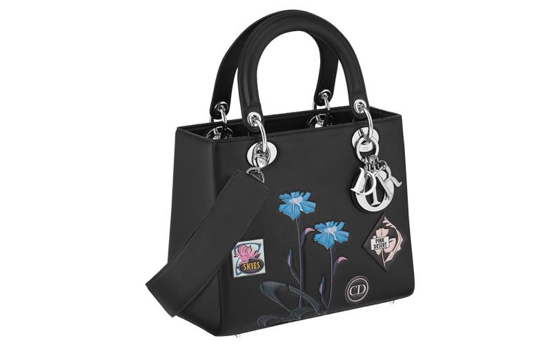 Sac « Lady Dior » en veau « paradise » noir, badges et fleurs en cuir embossé, bandoulière large.